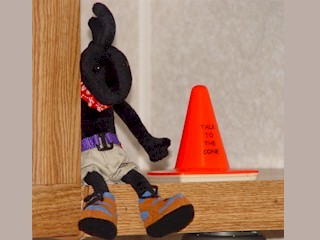 Kokopelli, at rest in his coach, with Coney the Traffic Cone at his side.