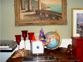 Kokopelli and Coney the Traffic Cone atop the Apple Power Mac G4 Cube, with C.Proietto painting in the background.