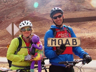 A couple, racing in the 2012 Adventure Xstream Race stops to visit with Plush Kokopelli on the Potash Road, Moab, Utah