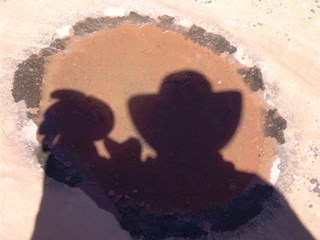 Plush Kokopelli and the Other, reflected in a pothole, somewhere in the Southwest