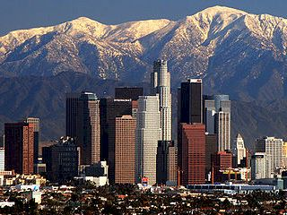 Winter scene of Downtown Los Angles, with the snowcapped San Gabriel Mountains beyond.
